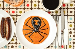 orange pumpkin pancakes with black cinnamon syrup and spiders